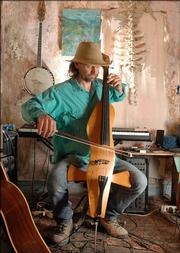 Karl Ramberg plays an electric cello he crafted with help from a friend. He played Tuesday in the music studio at his east Lawrence home.