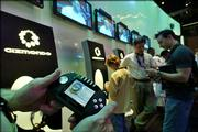Convention attendees examine Gizmondo, a multi-entertainment device, during the Electronic Entertainment Expo in Los Angeles. Gizmondo looks to be the Swiss-Army knife of hand-helds with a blend of technology that includes GPS satellite tracking, a digital camera and a gyroscope. It also plays digital music, movies and video games on a 2.8-inch color screen.