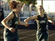 Free State High's Kaitlin Squier, left, takes the baton from Robyn Lee during the girls 3,200 relay at a Class 6A regional. FSHS was second in the event Friday at Olathe District Activities Center.
