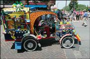 Richard Renner, of Lawrence, drives the Recycle Cycle in the annual Art Tougeau Parade through downtown Lawrence. Renner's ride claimed the grand prize Saturday afternoon.