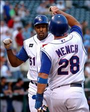 Texas' Richard Hidalgo is congratulated by teammate Kevin Mench after Hidalgo's home run against Kansas City. The Rangers beat the Royals, 4-3, Tuesday in Arlington, Texas.