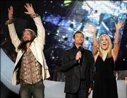 """American Idol"" finalists Bo Bice, left, and Carrie Underwood, right, wave to the crowd from the stage with the show&squot;s host, Ryan Seacrest, after their final performance. Viewers voted Tuesday night on the performance and the results will be announced tonight."