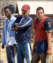 "Former Pro quarterback Paul Crewe (Adam Sandler), right, calls upon coach Nate Scarborough (Burt Reynolds), center, and Caretaker (Chris Rock), left, to help him field a football team of inmates to take on the guards in the comedy ""The Longest Yard."""