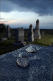 Three stones, representing visits to a grave, rest atop a tombstone.