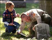 Dakota Zinn, 9, watches as his father, Rod, brushes off dust and mold growing on a headstone of a Civil War veteran at the Oak Hill Cemetery.   The Sons of Union Veterans local post -- Sgt. Samuel Churchill Camp No. 4 - decorated the graves of the more than 250 veterans with flags Saturday at the cemetery for Memorial Day.