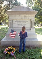 Dakota Zinn, 9, reads a memorial dedicated to the 150 Lawrence residents who were killed in William Quantrill's raid on Aug. 21, 1863.  Zinn, a Boy Scout with Pack 3462, helped decorate the graves of Civil War veterans Saturday at Oak Hill Cemetery.