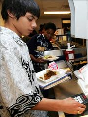 Marietta Middle School eighth-grader Merwing Olivares enters his code into a MealPay keypad in the line at the cafeteria of the school in Marietta, Ga. Students enter their codes into a MealPay keypad when they purchase their food and then their parents are able to see what they bought for lunch via a computer terminal and the Internet.