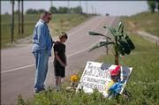 Michael Irvin, Lecompton, and his grandson, Jonathan Irvin, 8, from Superior, Neb., pause Saturday morning at a roadside memorial where Michael's wife, B.J., was killed in a car wreck last week. The site is on County Road 1029 just south of Lecompton.