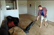 In his nearly bare apartment, Ben Parrott vaccums the floor of his living room before vacating it for the summer. Parrott, who pays $400 each month plus utilities for the space, hopes to sublease the apartment for the summer.  He cleaned up on Friday.