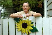 Master Gardener/ Jack Landgrebe rests on his side gate. Landgrebe's garden is part of the 2005 Douglas County Garden Tour, scheduled for Saturday and Sunday in Lawrence.