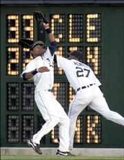 Detroit center fielder Nook Logan, left, avoids right fielder Craig Monroe to catch a fly ball hit by Texas' David Dellucci. The Tigers defeated the Rangers, 6-4, Wednesday night in Detroit.
