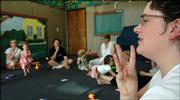 "Instructor Sarah Long demonstrates the sign for ""water"" during a lesson at the Music Clubhouse, 2201 W. 25th St. The parents and their young children together learn sign language for simple everyday words and actions."