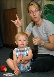 Jean Anderson, Lawrence, learns some American Sign Language with her 18-month-old son, Joshua, in a class at the Music Clubhouse, 2201 W. 25th St. A growing number of parents and their young children are learning to incorporate signing everyday words and actions into their communication skills.