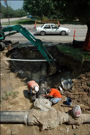 Reyes Manzanares, left, and Oscar Ortiz fasten together a water main near Sixth and Vermont streets in this file photo.