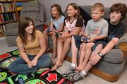 Free State High School senior Sally Campbell, 16, far left, baby-sits for a summer job. She sits with her charges, from left on couch, Harley Phelps, 9, Kristen Gile, 9, and Mason Phelps, 5, as well as her brother Ian Campbell, 15, as the kids played video games.