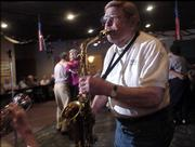 Clyde Bysom     performs with the Junkyard Jazz Band during a set at the American Legion on Thursday night. He, John Weatherwax and the late Don Scheid will be    honored Wednesday evening at the Lawrence City Band Concert at South Park.