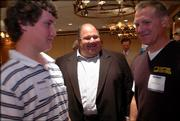 Kansas University football coach Mark Mangino, center, visits with Derec Olson, left, and his father Todd Olson after a Lawrence Chamber of Commerce breakfast. Mangino spoke Tuesday at the Hereford House about the 2005 season and fielded questions from the audience.