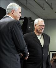 L.A. Lakers general manager Mitch Kupchak, left, greets Phil Jackson at a news conference. Jackson, let go by L.A. last summer, was rehired by the Lakers on Tuesday. The 60-year-old Jackson agreed to a three-year contract that reportedly will make him the highest-paid coach in NBA history.