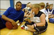 Kansas University sophomore-to-be C.J. Giles talks with Drew Henderson, of Kentucky, one of the campers at KU coach Bill Self's basketball camp. Giles was chatting Tuesday at Horejsi Center.