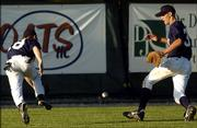Lawrence Outlaws outfielders Travis Hart, left, and Nick Ayre can't catch up with a pop fly against Mac-N-Seitz. The Outlaws lost twice, 8-3 and 10-0, Tuesday night at Free State High.