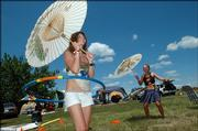 Jennifer Koss, left, and Christina Sampson, both from Marion, Mass., hula-hoop under the shade provided by an umbrella at the Wakarusa Camping and Music Festival Clinton State Park. The duo plans to camp all weekend long at the four-day festival.