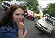 Melissa Senatore stands in the driveway of her home in Riverhead, N.Y., with four of the five vehicles her family owns. Senatore was paying more than $14,000 a year for auto insurance on the cars, but has gotten the bill down to near $10,000.