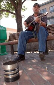 "Steve Burton plays guitar for tips on the northeast corner of 10th and Massachusetts streets in this 2005 photo. City commissioners approved ""aggressive panhandling"" ordinances, but they&squot;ve been rarely enforced. Burton says he has never had complaints about his playing music for donations."