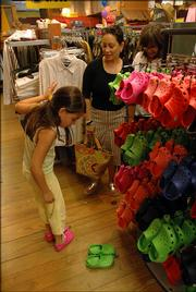 Paloma Garcia tries on a pair of Crocs as her mother, Anamaria Dickey, center, of Leawood, and Lisa Kobrber, of Lawrence, look on at Shark's Surf Shop, 813 Mass.