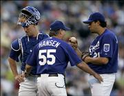 Kansas City pitching coach Guy Hansen, center, talks to pitcher D.J. Carrasco, right, and catcher John Buck during the first inning against Houston. Carrasco allowed just three runs in seven innings, but the Royals lost to the Astros, 6-2, Saturday night in Kansas City, Mo.