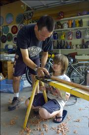 Bob Gent and his son, Ian, 10, work on a wooden sword Thursday in their workshop. Gent, a local glass artist, raises two kids, Ian and Helen, 13.