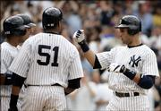 New York's Derek Jeter, right, is congratulated by teammate Bernie Williams (51) after hitting his first career grand slam. The Yankees defeated the Cubs, 8-1, Saturday in New York.