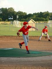 Cardinals pitcher Nate Bowman, left, throws the first pitch in a game July 13, between the Cardinals and Raptors of the 12-U Douglas County Amateur Baseball Assn. The Cardinals defeated the Raptors 22-4.