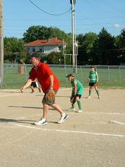 Thunder coach Brett Morris throws a pitch in a 10-U Lawrence Girls Fast Pitch Assn. game June 14 at Lawrence High.  League rules allow the coach to come into the game and pitch when the count reaches four balls.