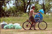 Ryan Shaughnessy, 19, Lawrence, helps with cleanup at Clinton Lake State Park after the festival. He peddled around the campgrounds Monday morning, filling his bag with cans.