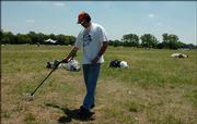 Ron Thomas uses a metal detector at the Wakarusa Music & Camping Festival site in hopes of picking up the spoils of the four-day series of concerts at Clinton Lake State Park.
