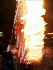 A protester burns an American flag to protest President Bush's second inauguration during a march in Portland, Ore., in this January 2005 file photo. The House on Wednesday approved a constitutional amendment that would give Congress the power to ban desecration of the American flag.