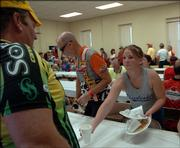 Jill Martin, a Perry-Lecompton senior and cheerleader, helps wait tables for cyclists at the Lecompton Community building. Lecompton was the first stop on the inaugural Border Raiders tour covering 400 miles through four states, beginning and ending in Lawrence.
