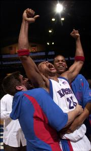 Kansas University's Wayne Simien, center, hoists his arms in the company of Stephen Vinson, left, and C.J. Giles after the Jayhawks beat Oklahoma State. Simien is expected to be a first-round pick in Tuesday's NBA Draft.
