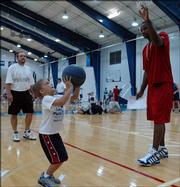 Six-year-old Reser Hall shoots as his father, Dick, of Prairie Village, left, and Kansas University sophomore Darnell Jackson, right, watch. The pair attended KU coach Bill Self's Parent-Child Basketball Camp on Saturday at Horejsi Center.