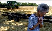 Clea Lee, 77, walks in a cut wheat field as her husband's crew prepares to move equipment to another field. This year marks the couple's 54th harvest.