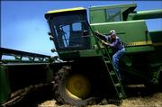 Jim Lee climbs onto his combine June 18.