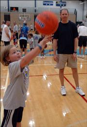 Former Kansas University basketball player Chris Piper watches his daughter Madison, 6, shoot the ball during drills. They attended the Bill Self Parent-Child Basketball Camp on Saturday at Horejsi Center.