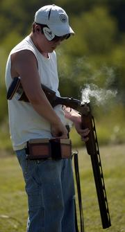 Twelve-year-old Bryan Hull loads his shotgun during a trapshooting session. The Wellsville native practiced last week at Cedar Hill Gun Club near Baldwin.