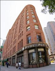 Pedestrians pass by the Brown Palace Hotel in downtown Denver. The hotel serves tea every afternoon.
