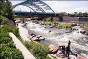 People watch from the banks of the South Platte River as a couple of kayakers make their way through the white water. The river is a short distance from the western end of 16th Street, across the Millennium Bridge.