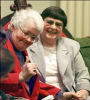 Lois Farnham, left, gives a thumbs up as she holds the hand of Holly Puterbaugh in the Vermont House chamber in Montpelier, Vt., April 25, 2000, as the civil unions bill passed. The two women were one of the original three couples who brought suit against the state.