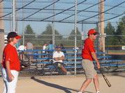 Harrison Helmick, left, assists Reds head coach Larry Leslie warm up the infield before their Jhawk baseball league matchup with the Cubs. The Friday game at Holcom became a scrimmage because the Cubs only had four players.