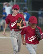 Cardinals Emily Peterson and Dylan Scott hustle off the field.