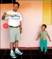 Kansas University volleyball coach Ray Bechard plays with a boy in Sao Paulo, Brazil. The Jayhawks traveled to Sao Paulo and Rio de Janeiro after the spring semester to bond, have fun and learn about Brazilian culture.