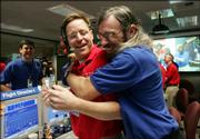 Dan Kubitschek, left, and Steve Collins celebrate the collision of NASA's Deep Impact spacecraft with the comet Tempel 1 Sunday night in Mission Control at the Jet Propulsion Laboratory in La Canada Flintridge, Calif.